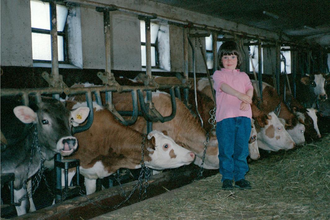 Denise als Kind im Kuhstall