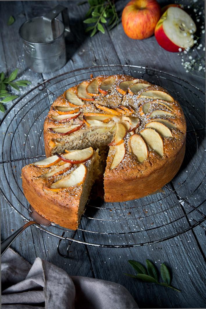 Angeschnittener gesunder Apfelkuchen auf Kuchengitter in dunklem Setting.
