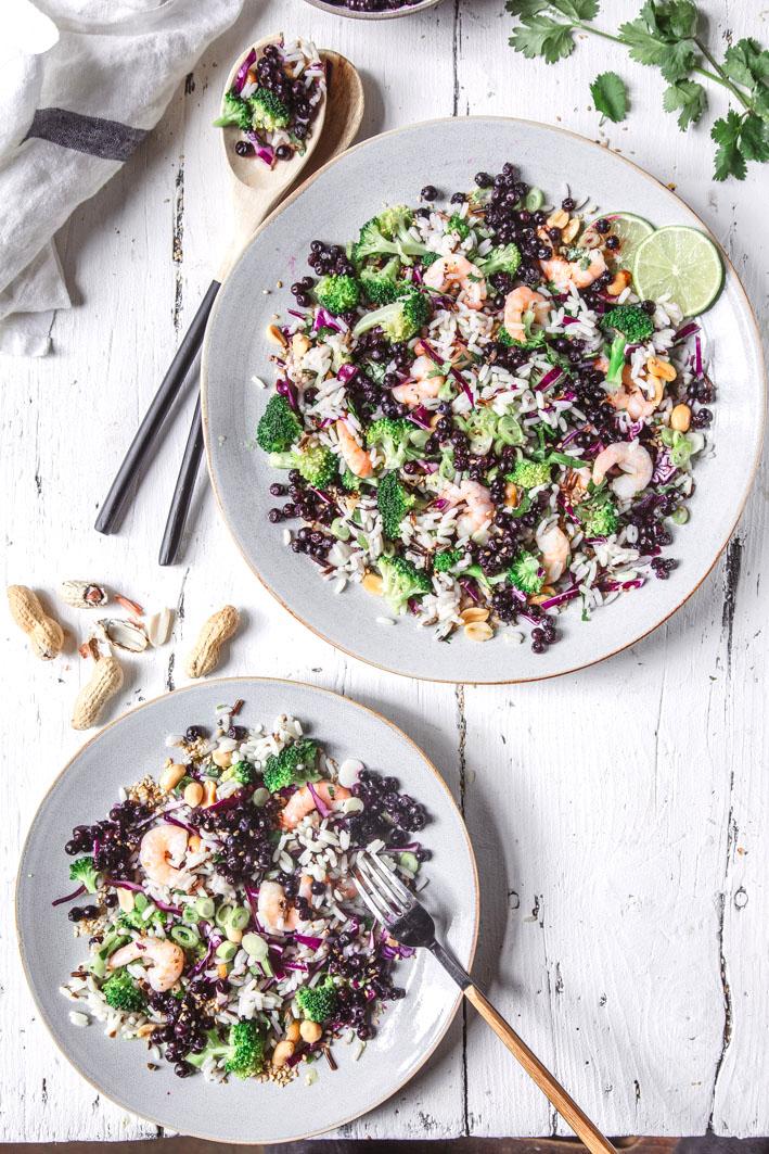Asiatischer Reissalat mit wilden Blaubeeren, Broccoli, Erdnüssen und Shrimps