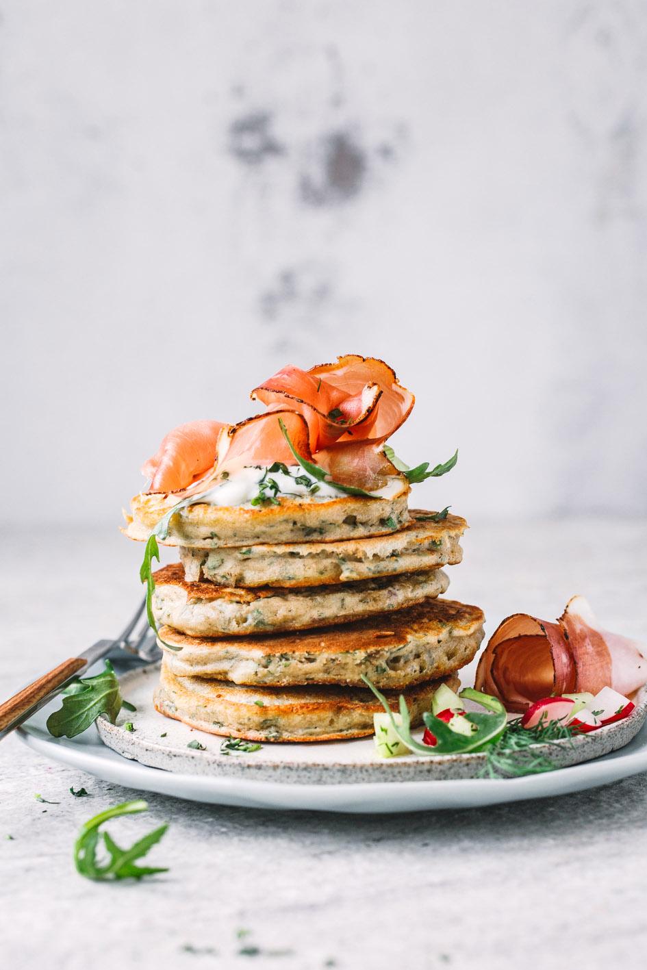 Zucchini-Kräuter-Pancakes übereinandergestapelt mit Speck auf Teller