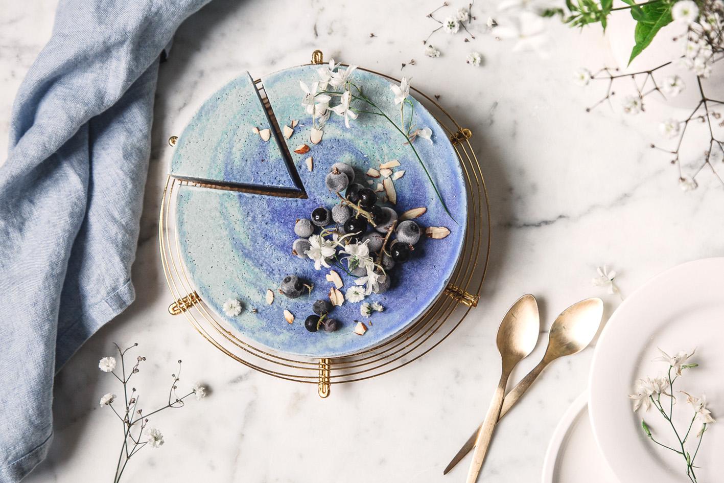 Angeschnittene blaue Eistorte mit Blaubeeren auf Marmortisch.