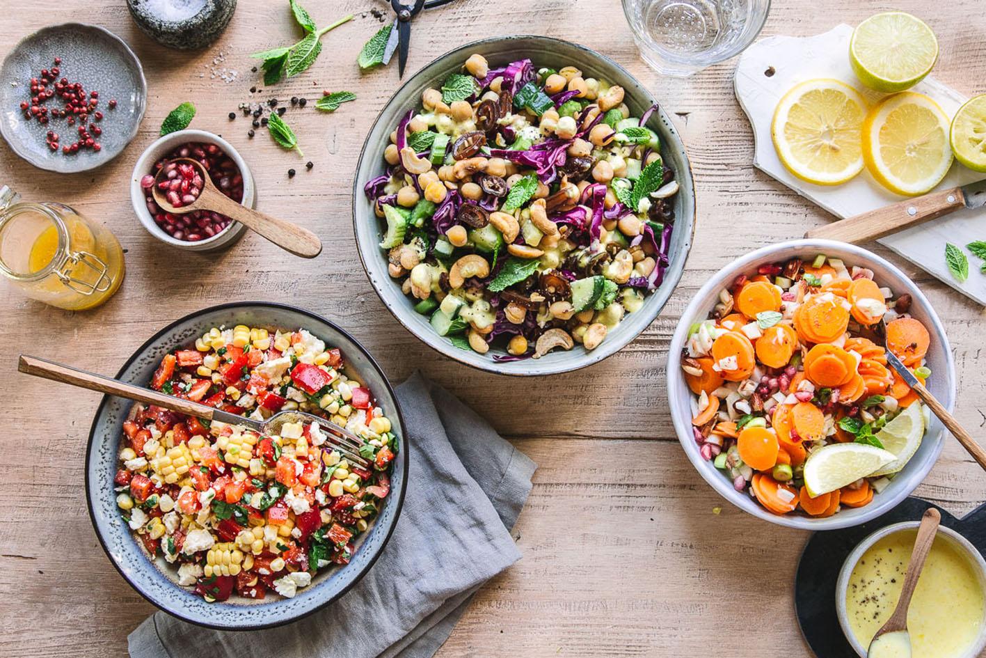 Drei Grillsalate in Schüsseln mit Zutaten auf Holztisch