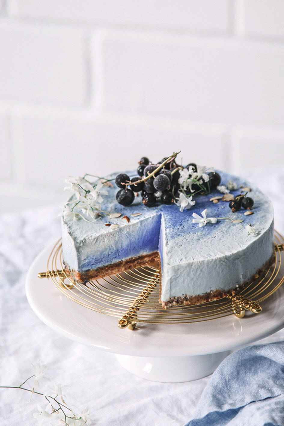 Blaue Eistorte mit Blaubeeren dekoriert auf Kuchengitter und Tortenplatte.
