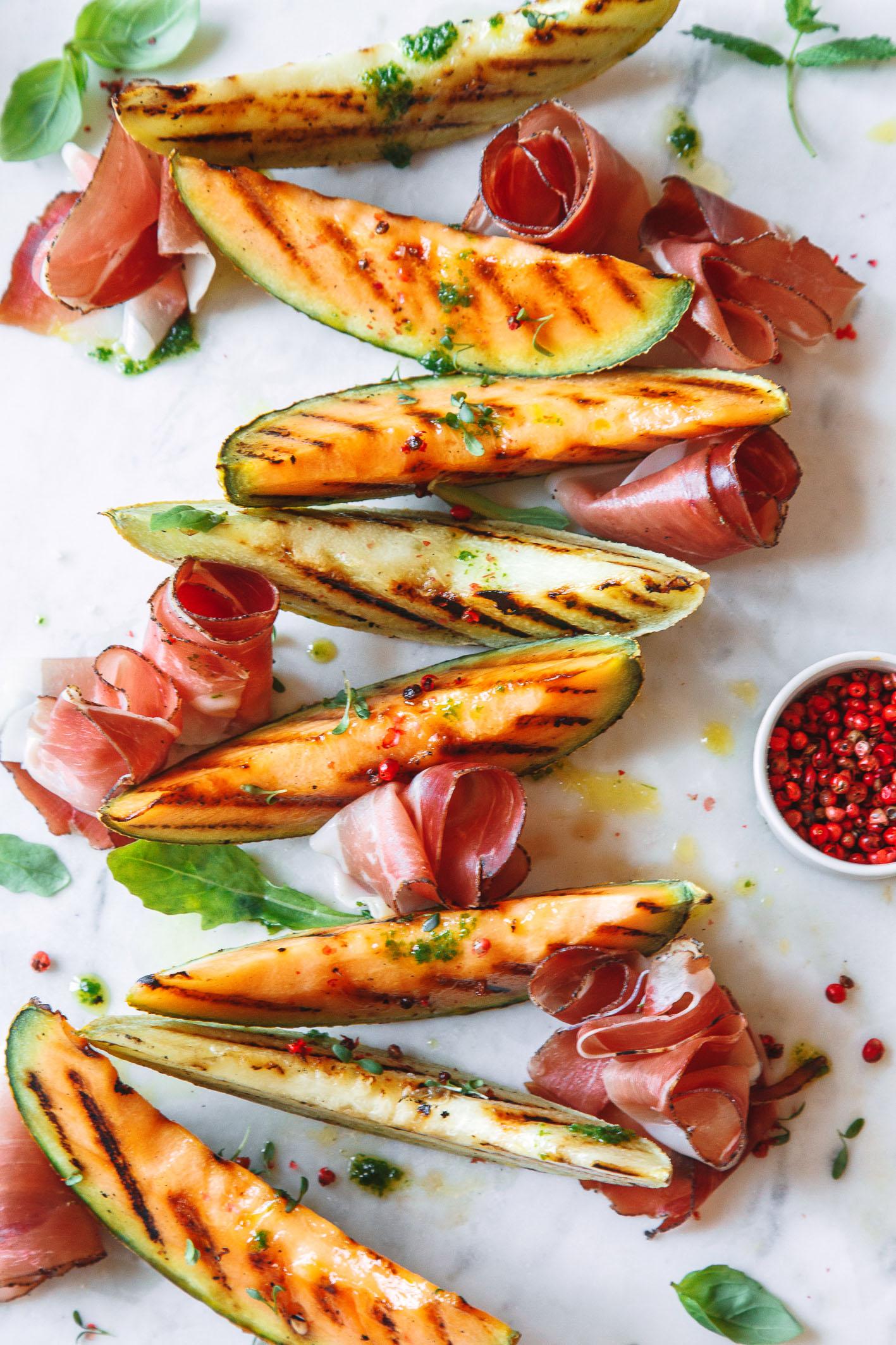 Gegrillte Melonenspalten mit Speck und Pesto auf weißer Platte