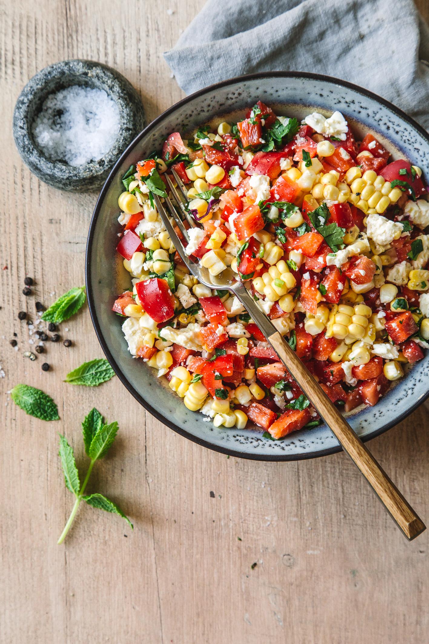 Mais-Paprika-Feta-Salat in Schüssel mit Gabel auf Holztisch