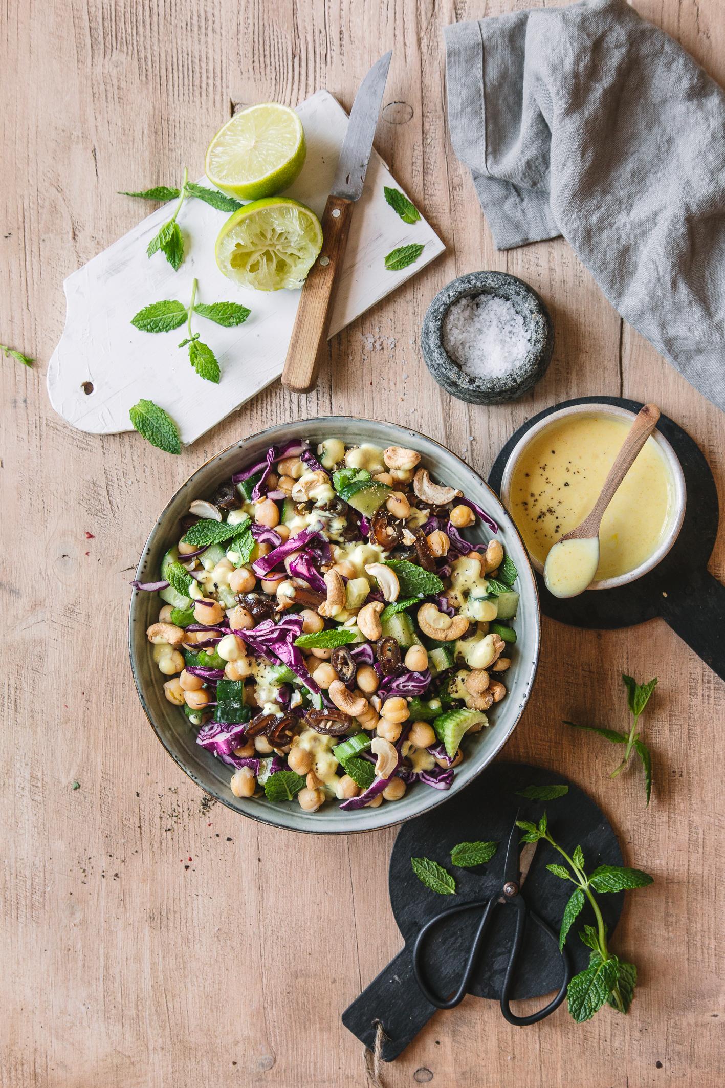Kichererbsen-Rotkohl-Salat in Schüssel mit Dressing und Limetten auf Tisch