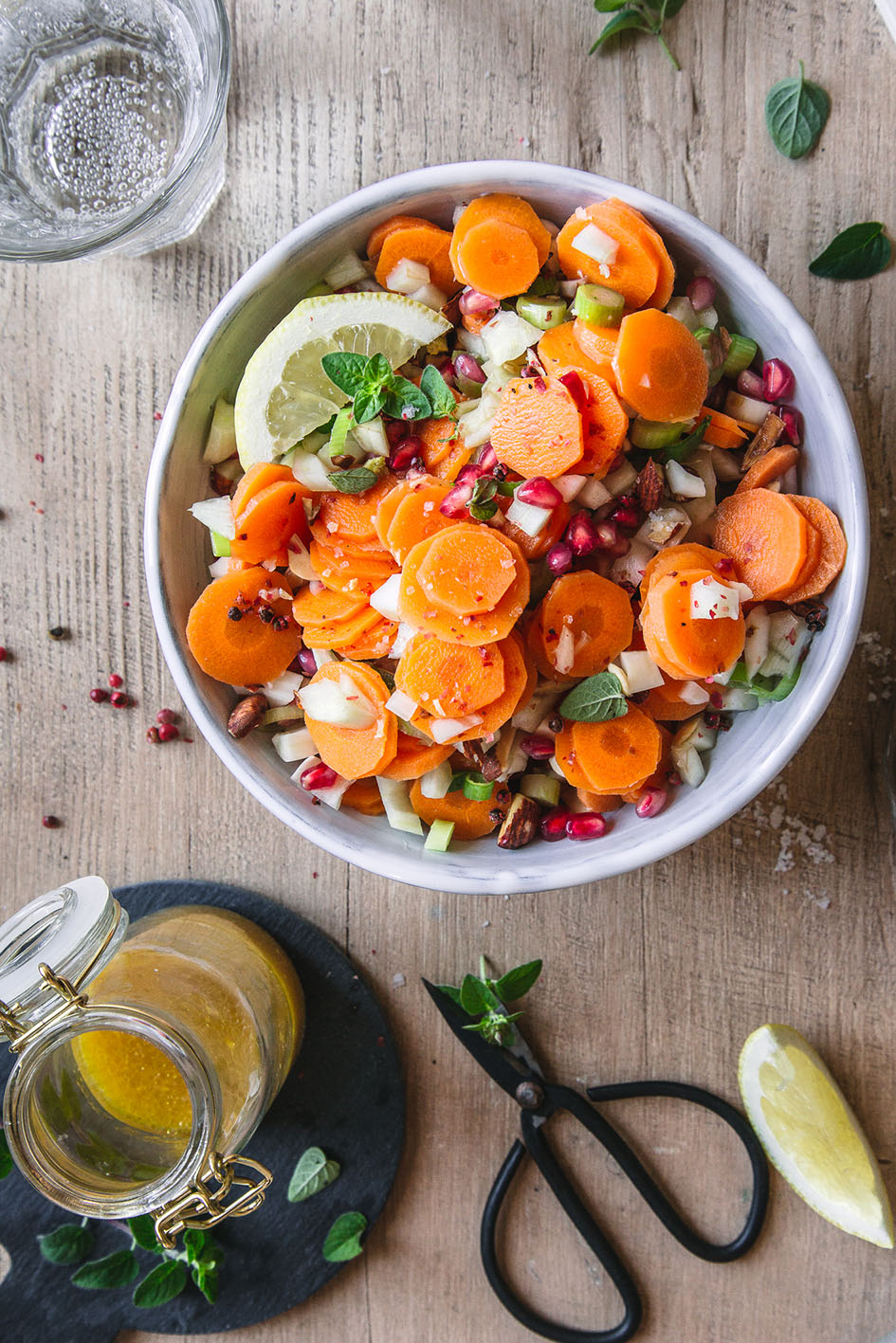 Möhren-Fenchel-Salat in weißer Schüssel mit Dressing in Flasche
