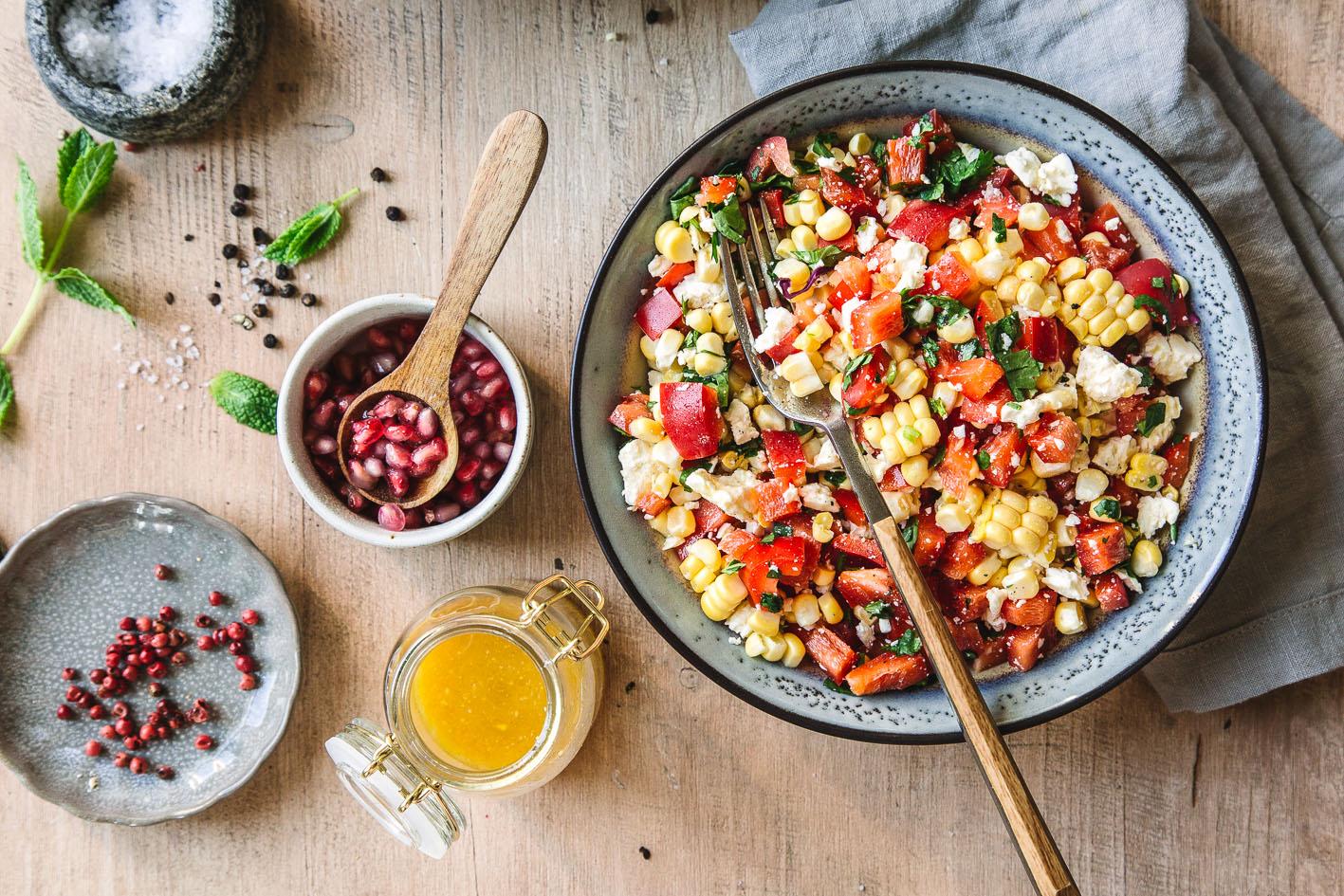Mais-Paprika-Salat mit Dressing auf Holztisch