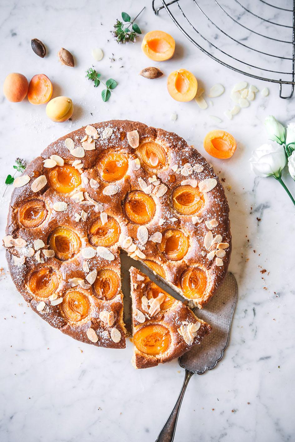 Angeschnittene Aprikosen-Mandel-Tarte mit Tortenschaufel auf Marmorplatte