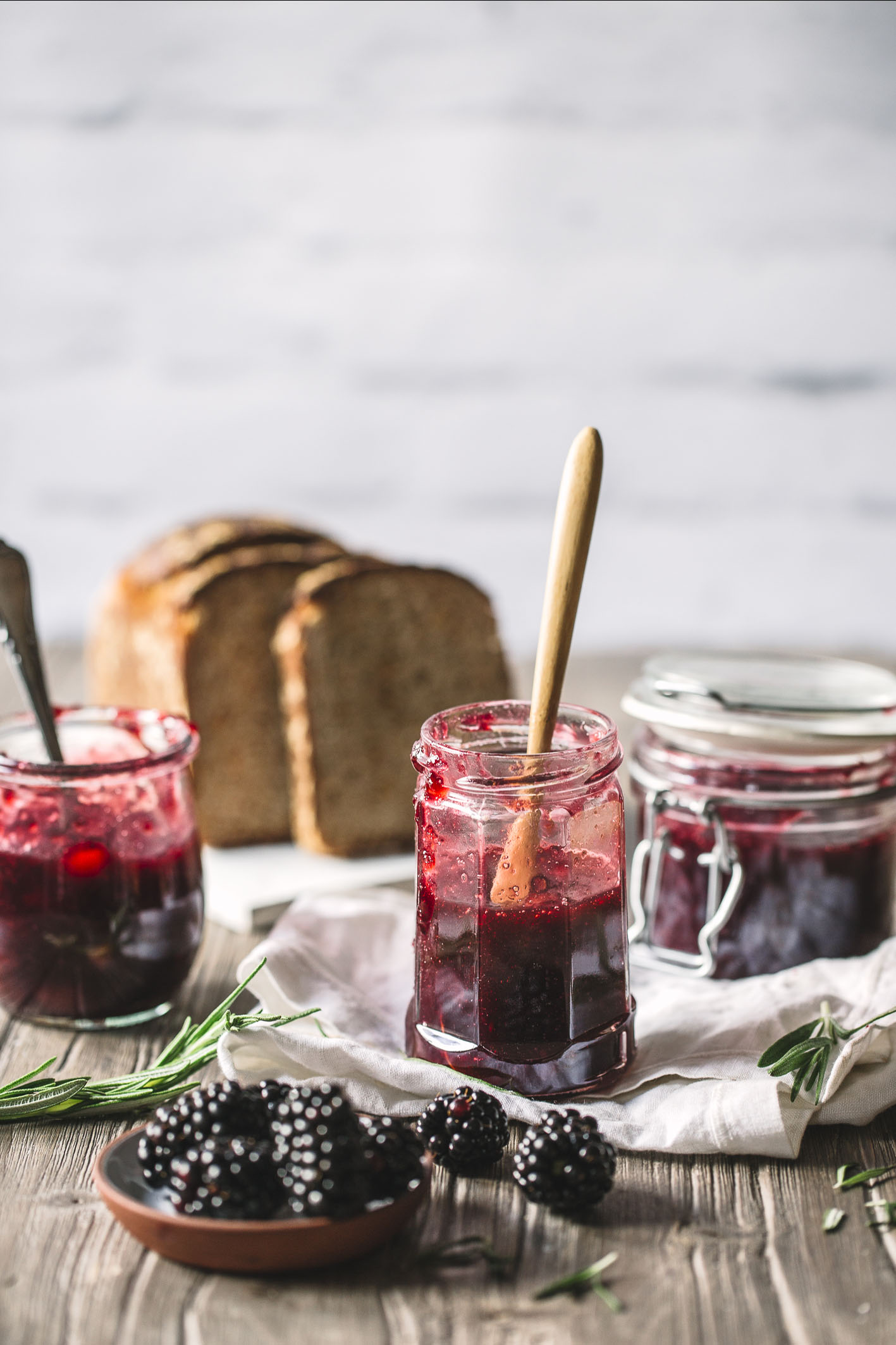 Apfel-Brombeer-Marmelade in drei Gläsern auf Holztisch