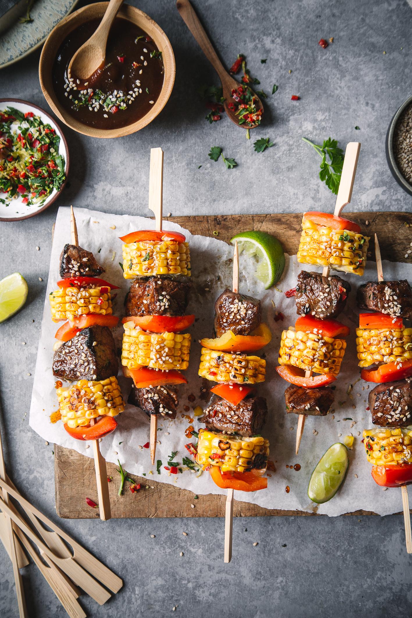 Mais-Paprika-Rindfleisch-Spieße auf Holzbrett mit Marinade in Schüssel