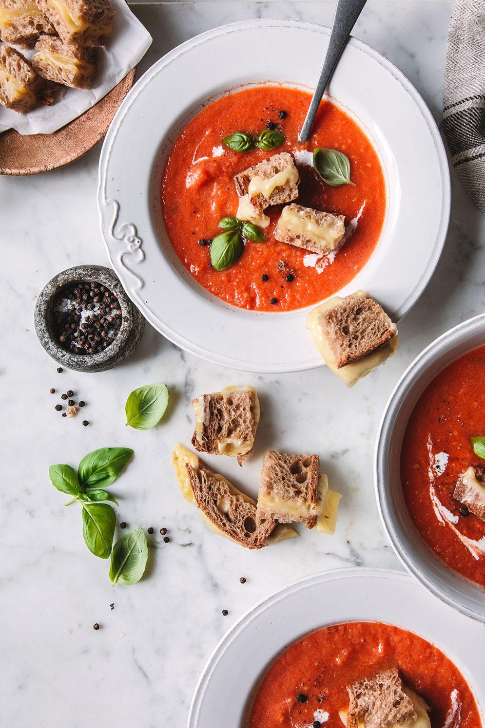 Zwei Teller sowie Topf mit Tomatensuppe und Käse-Croûtons