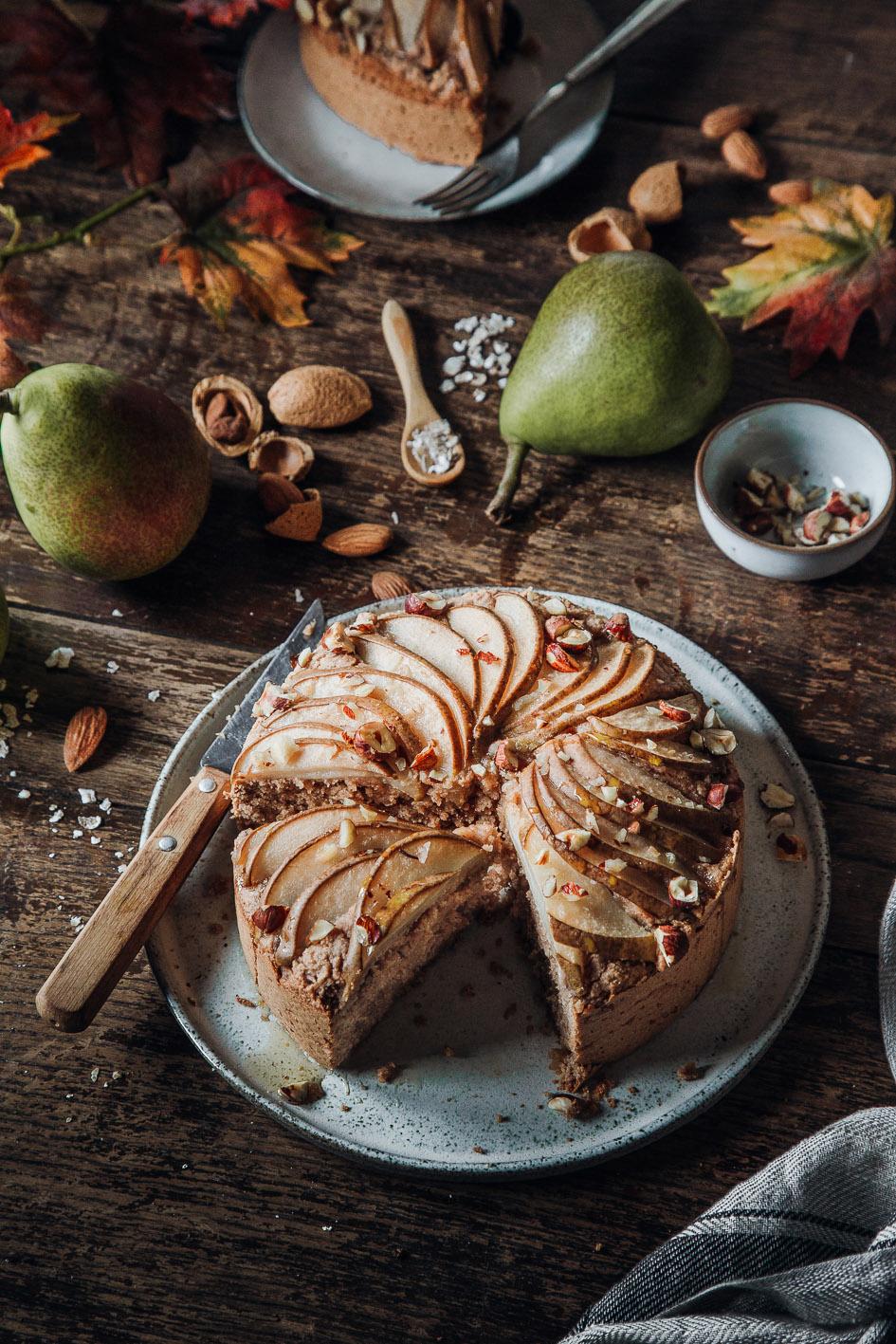Angeschnittener veganer Birnenkuchen auf herbstlich gedecktem Tisch