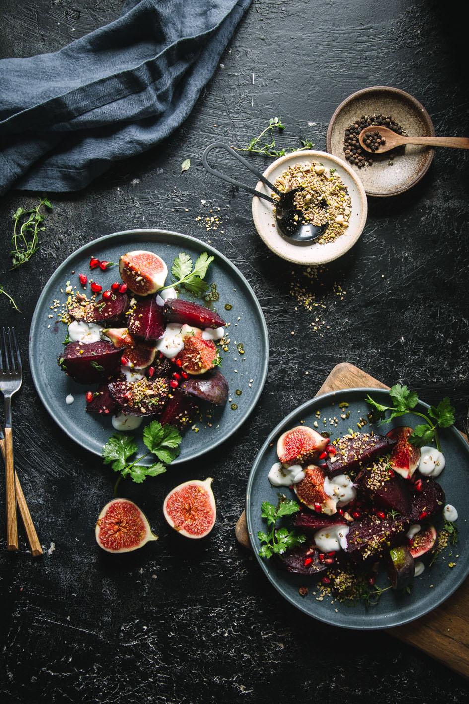 Zwei Teller Rote Bete Salat mit Feigen auf dunkler Platte gedeckt