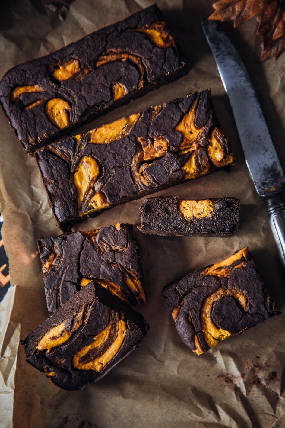 Angeschnittene Kürbis-Brownies mit Messer auf Backpapier