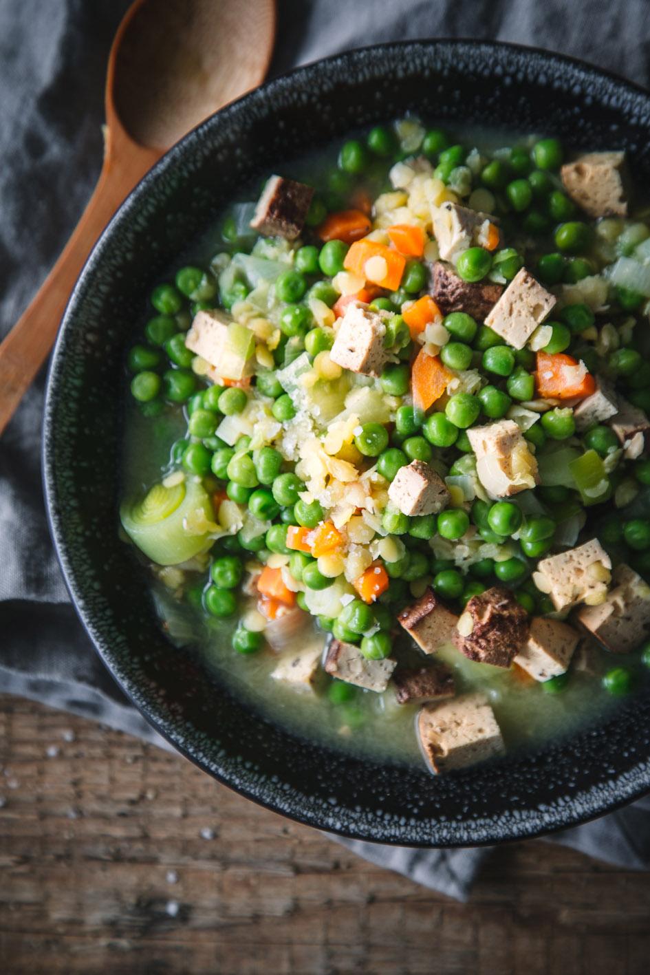 Veganer Erbseneintopf mit Räuchtertofu in Teller auf Holztisch