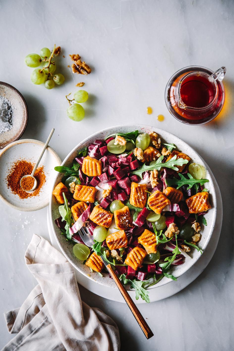 Süüßkartoffelgnocchi auf Salat mit Zutaten auf Marmortisch