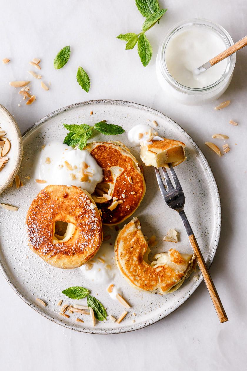 Gebackene Apfelringe auf Teller mit Joghurt und Gabel