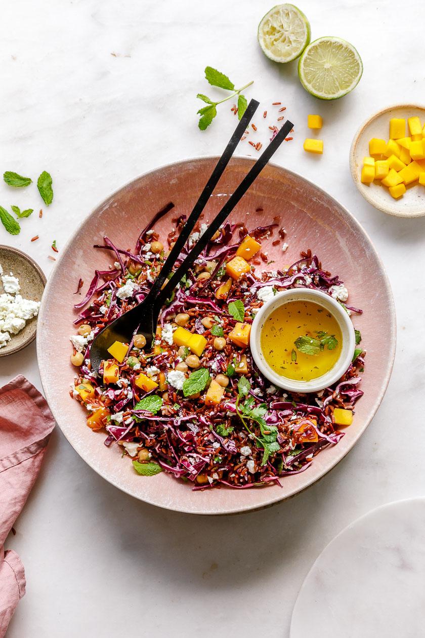 Reissalat mit Rotkohl und Mango in großer Schüssel mit Salatbesteck