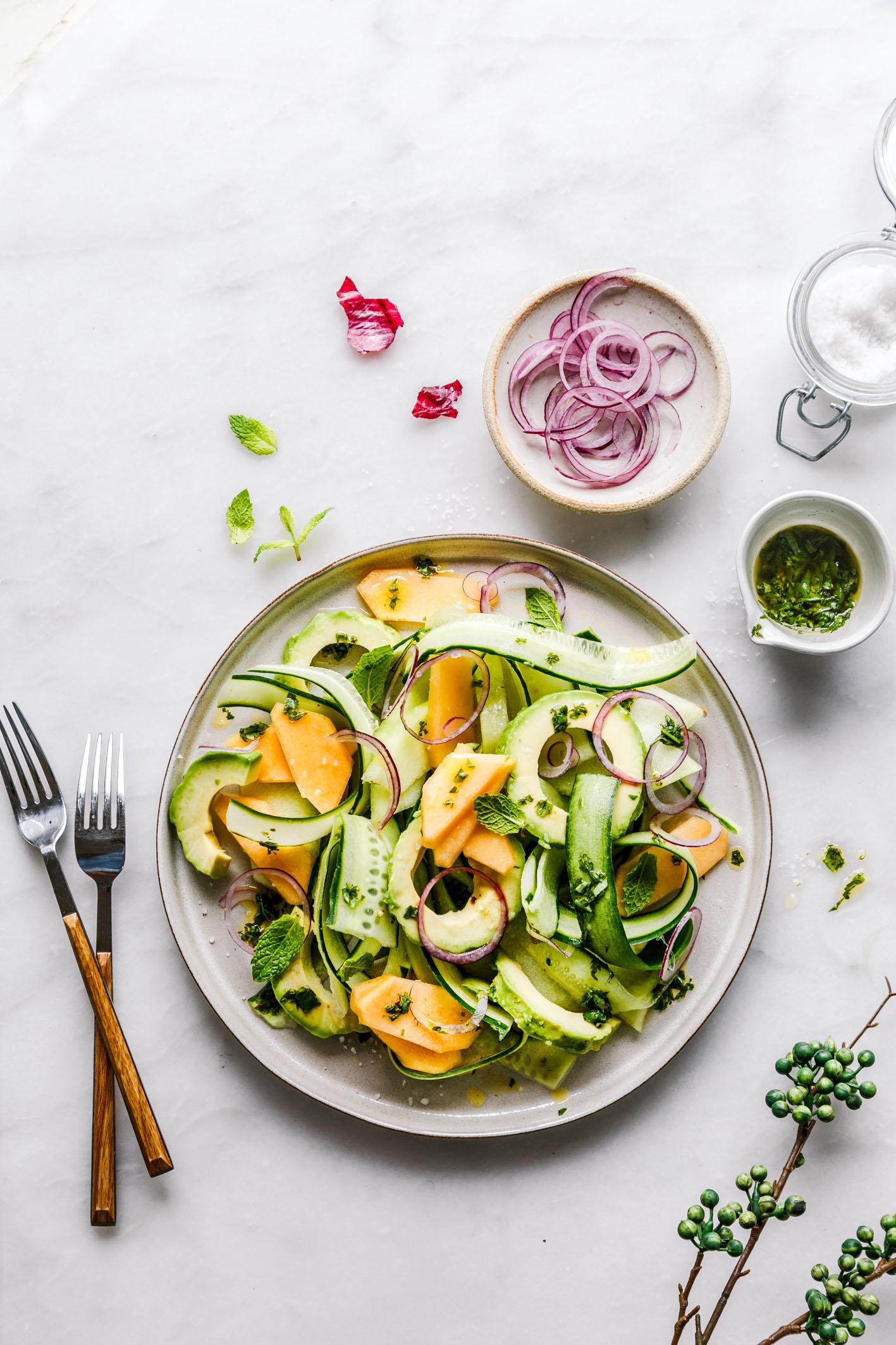 Melonen-Gurken-Salat auf Teller mit Besteck und roten Zwiebeln