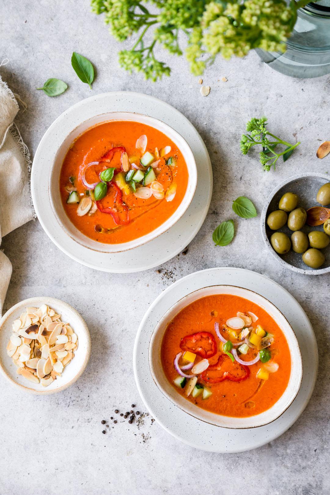 Zwei Teller mit kalter Paprikasuppe und Schälchen mit Oliven und Mandeln