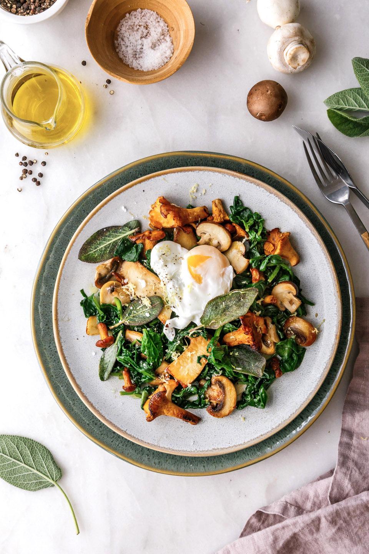 Pilzpfanne mit Spinat und pochiertem Ei auf gedecktem Tisch.