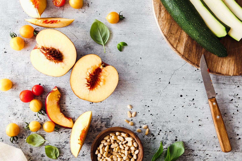 Zucchini, Pfirsiche, Pinienkerne und Tomaten auf Marmorplatte und Holzbrett