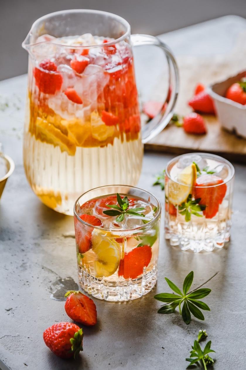 Karaffe und zwei Gläser alkoholfreie Maibowle auf Tisch