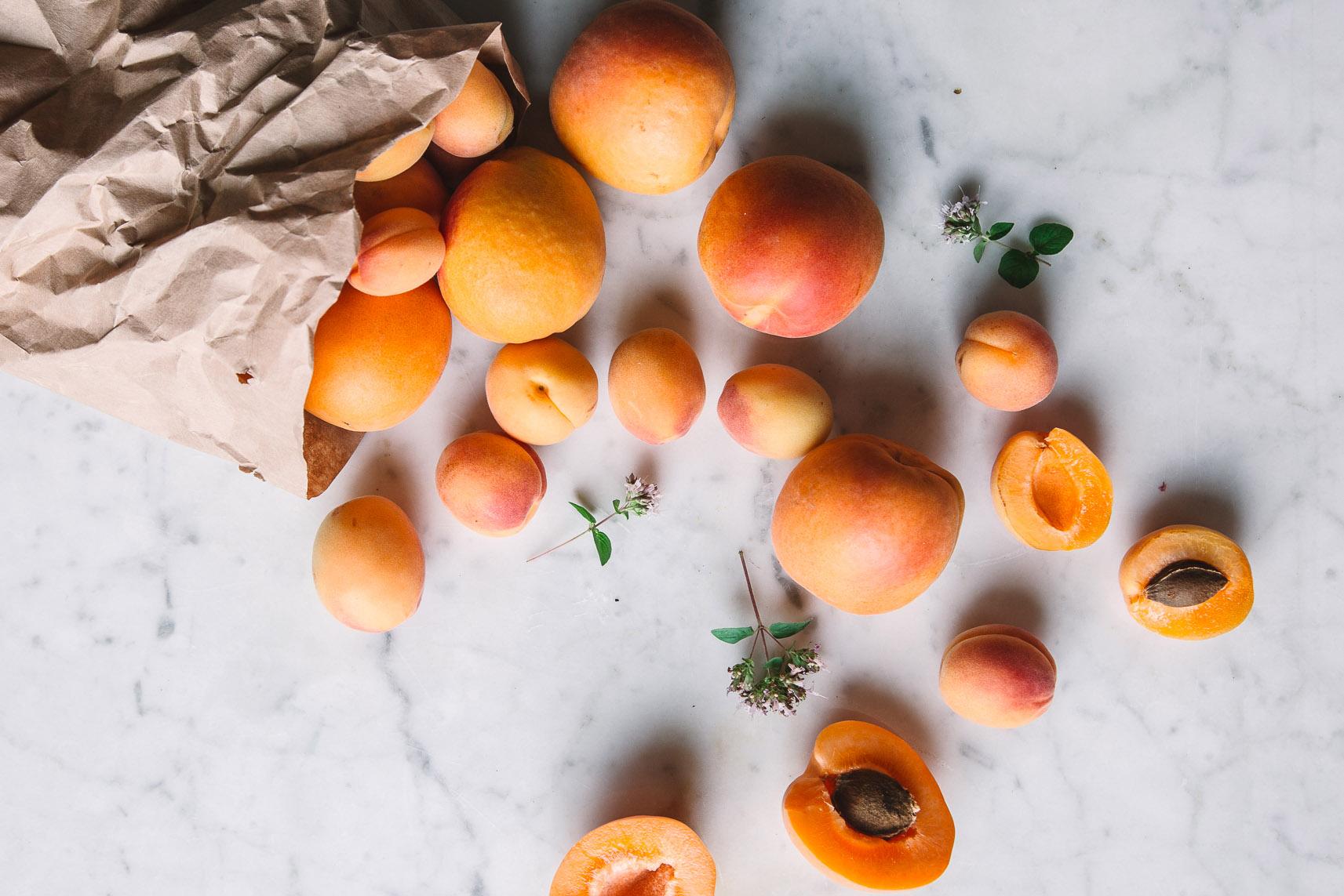 Aprikosen in Papiertüte und auf Marmortisch