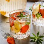 Zwei Gläser alkoholfreie Maibowle mit Karaffe im Hintergrund