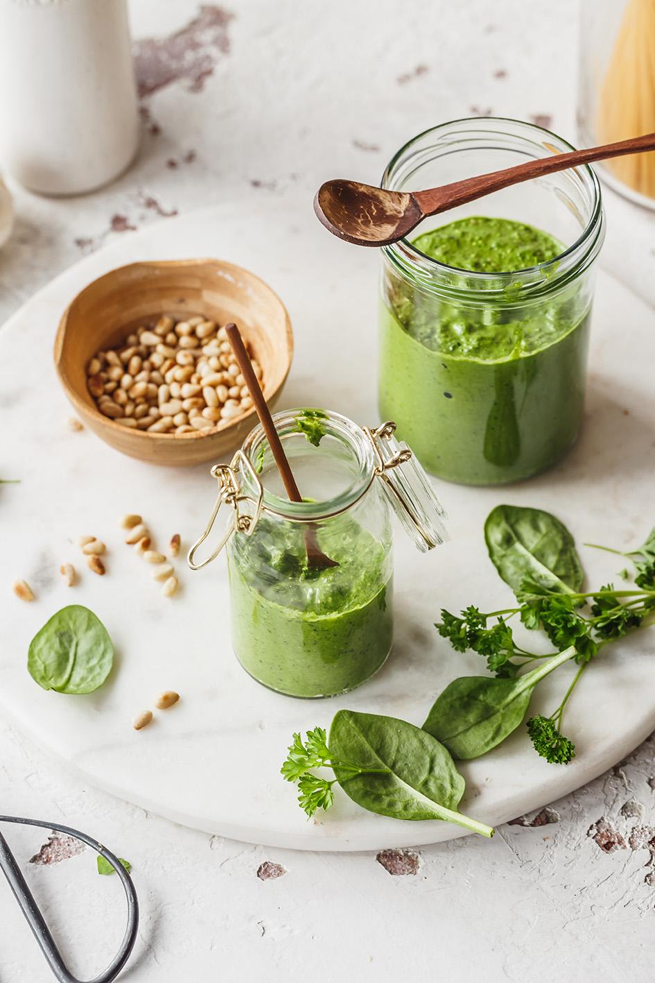 Veganes Spinat-Pesto in zwei Gläsern mit Holzlöffel