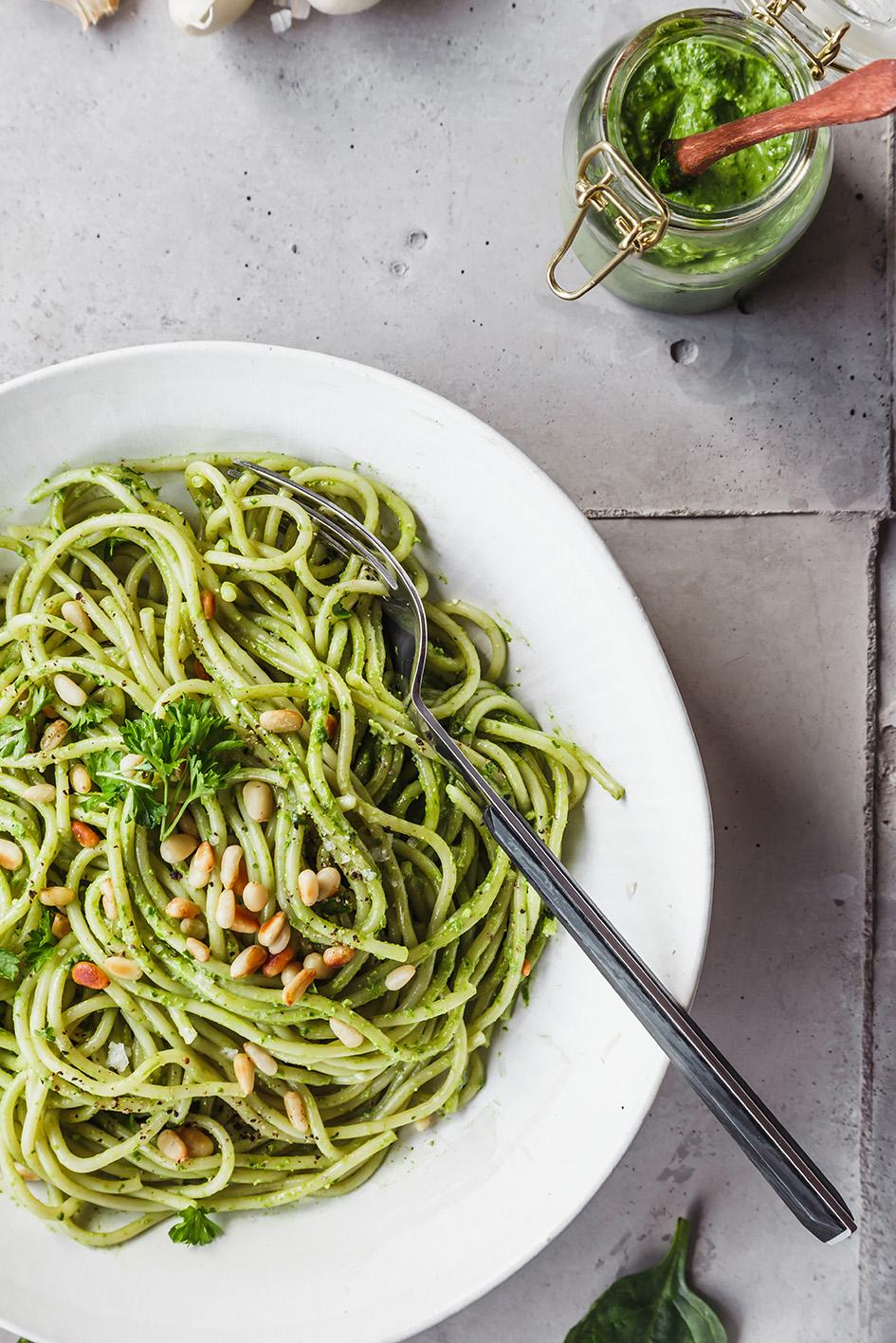 Veganes Spinat-Pesto im Glas und mit. Pasta auf Teller