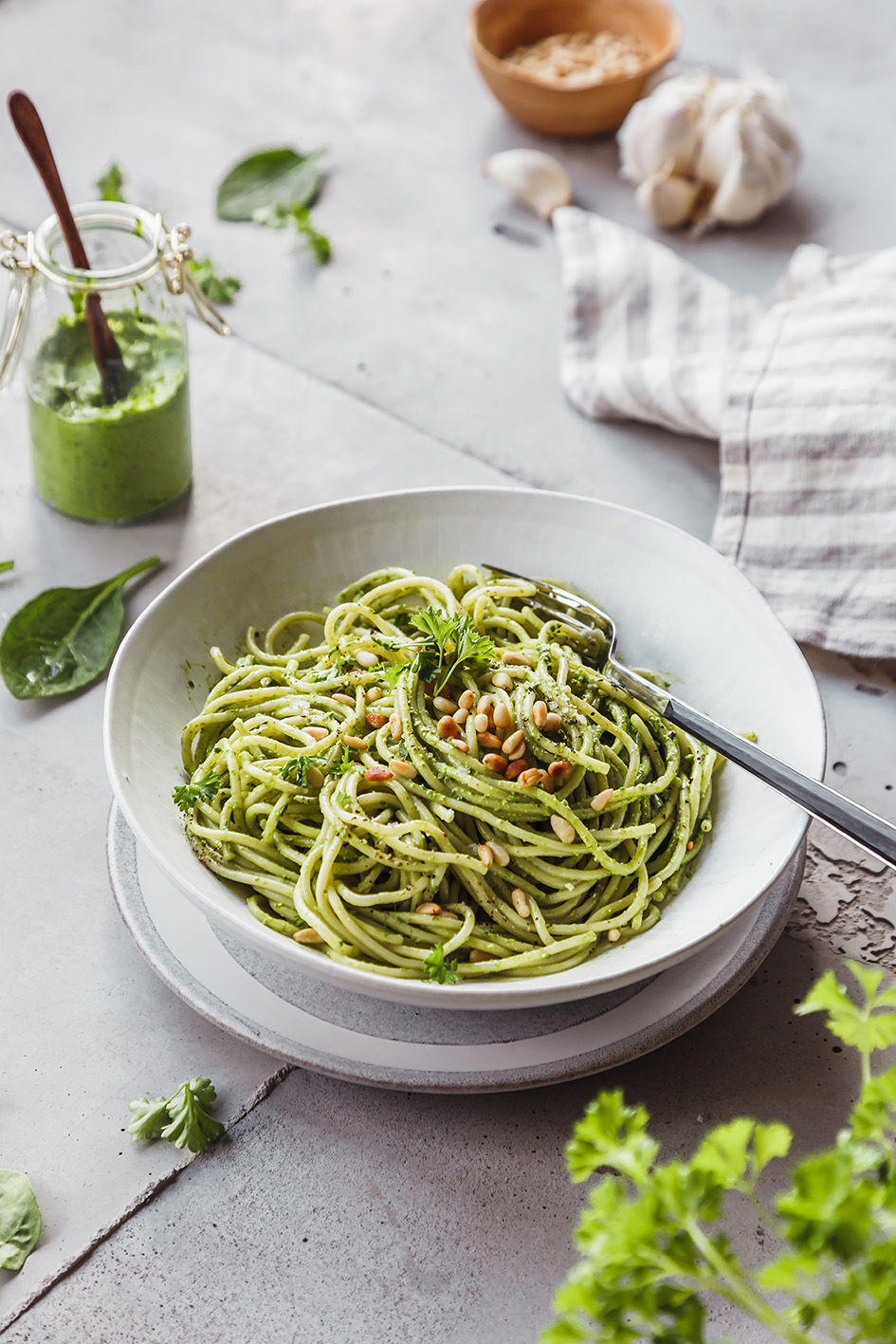 Ein Teller Spaghetti mit Pesto vermengt und Glas Pesto im Hintergrund