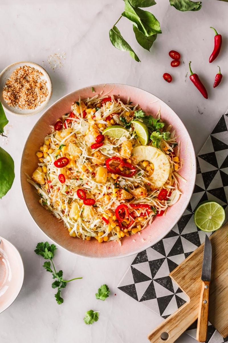 Veganer Weißkohlsalat mit Ananas, Paprika und Lauchzwiebeln in großer Schüssel