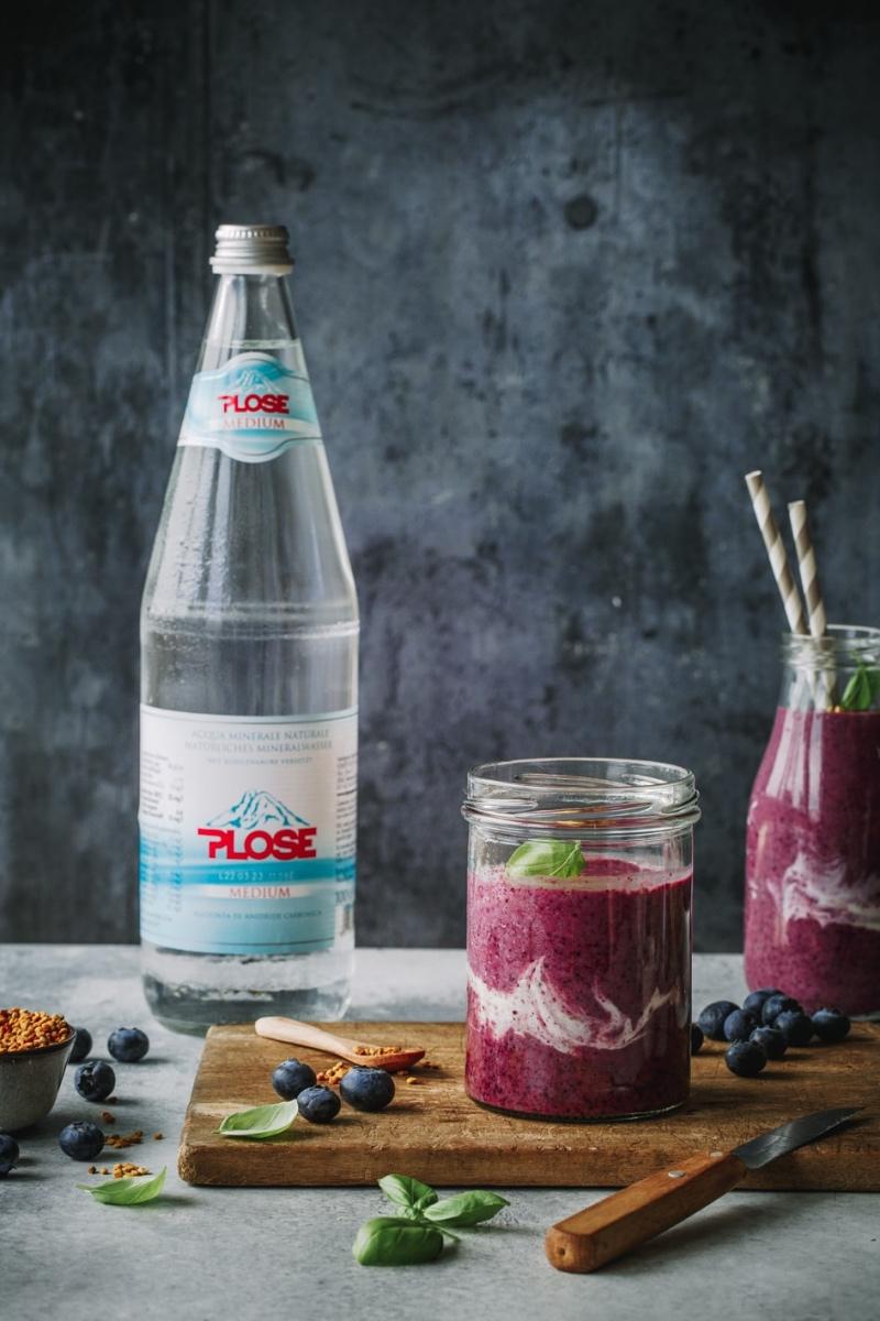 Zwei Gläser Blaubeer-Bananen-Smoothie mit Flasche Wasser