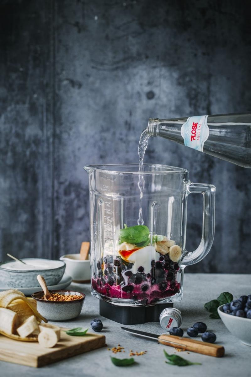 Zutaten von Blaubeer-Bananen-Smoothie im Mixer mit Flasche Wasser