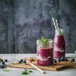 Glas und Flasche Blaubeer-Bananen-Smoothie mit Zutaten.