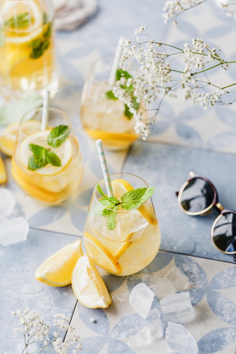 Zitronen-Eistee ohne Zucker in mehreren Gläsern mit Strohhalm auf blauen Fliesen.