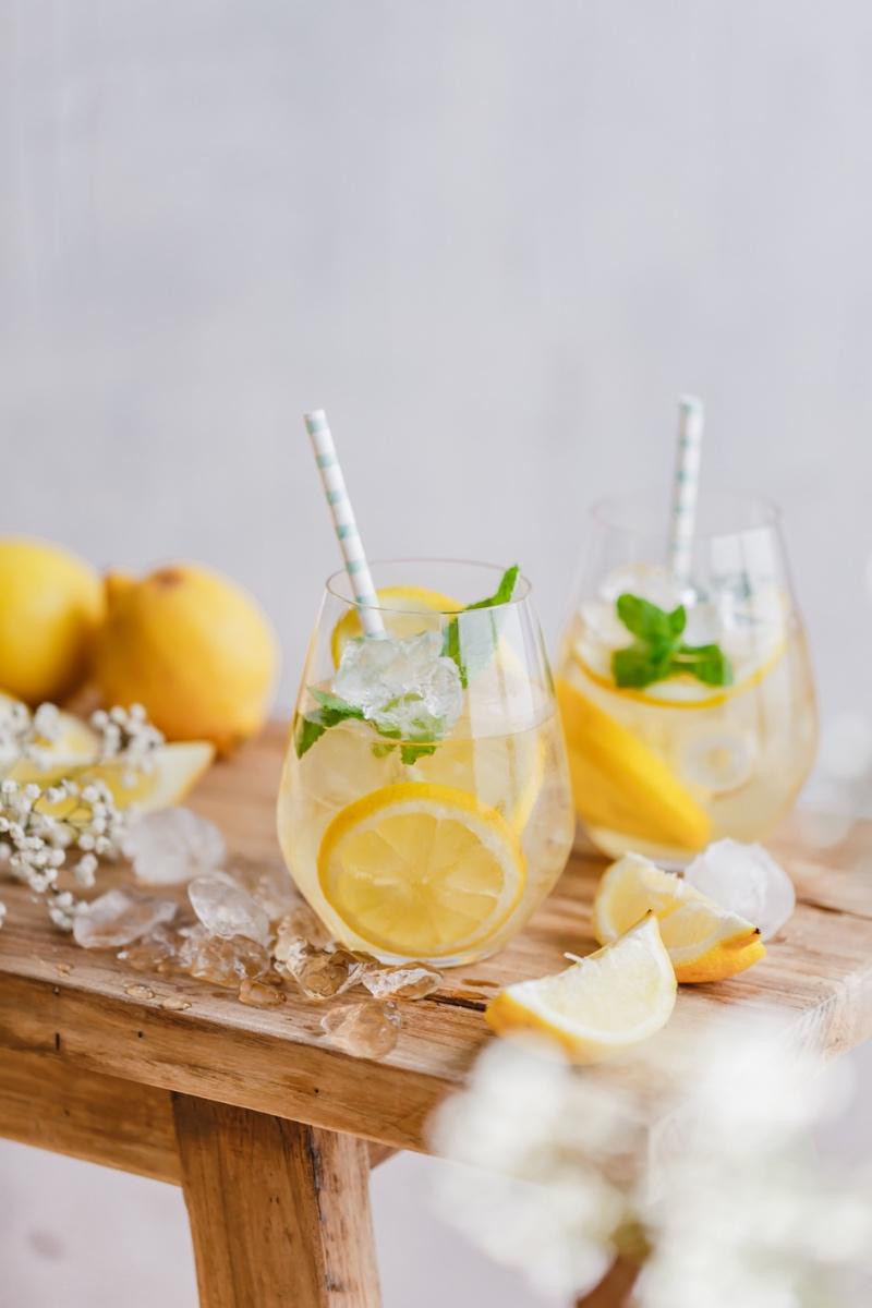 Zwei Gläser Eistee ohne Zucker und Zitronen auf Holzbank
