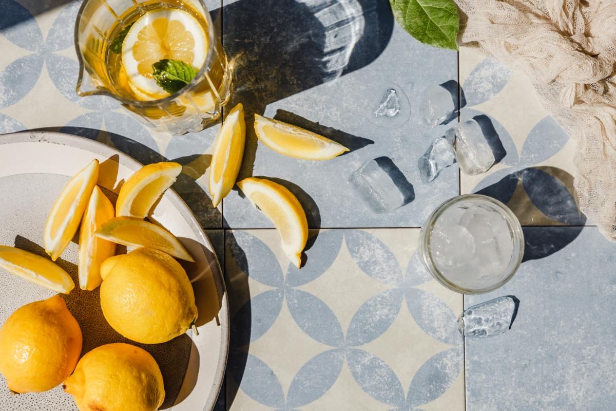 Eistee ohne Zucker in Karaffe und Glas mit Zitronen als Deko.