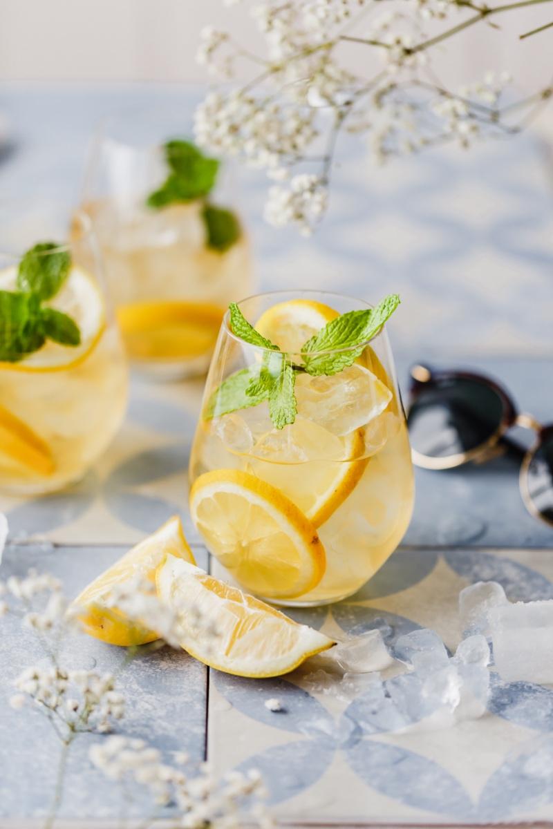 Zitronen-Eistee ohne Zucker im Glas mit Zitronenschale.