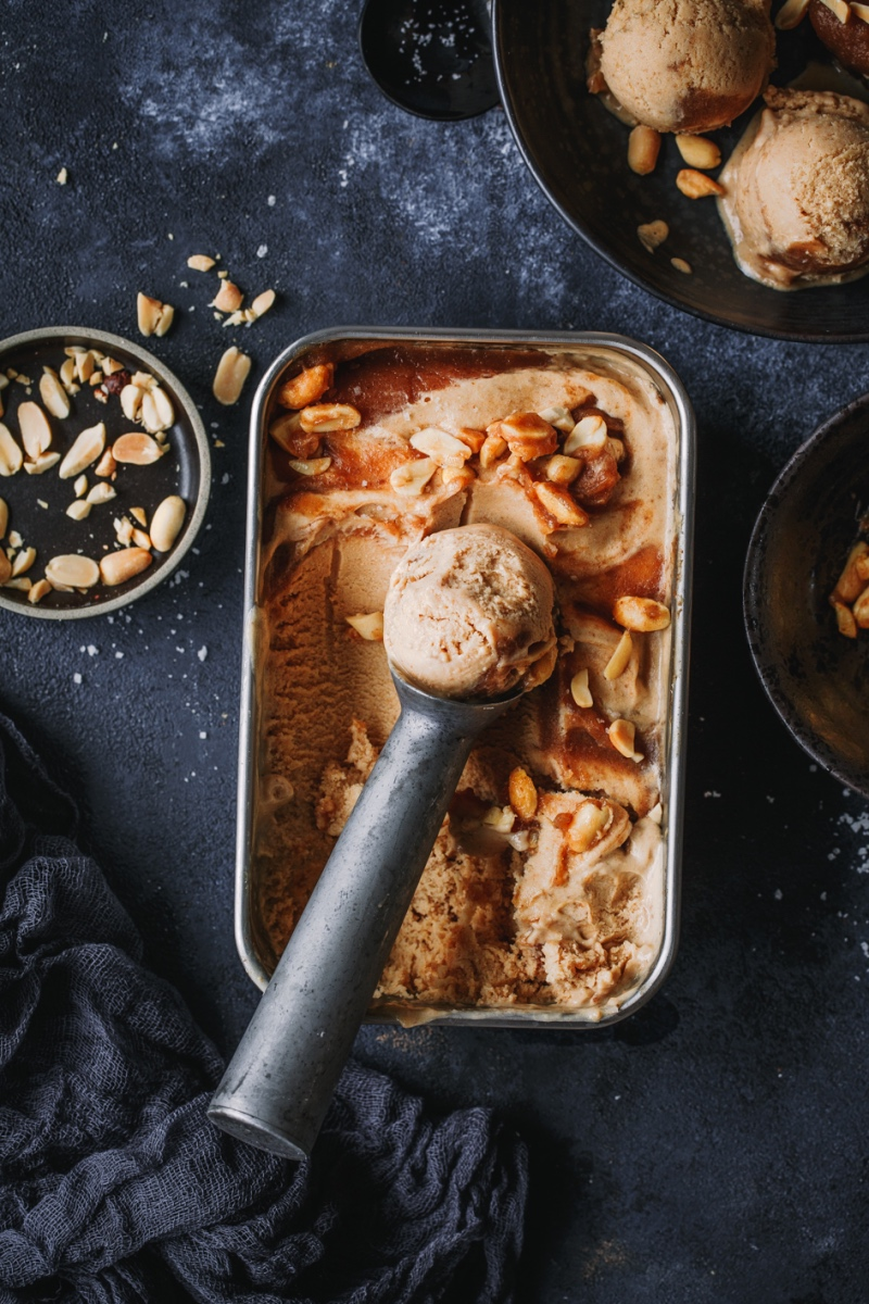 Erdnusseis mit Karamell in Dose und Eisportionierer auf schwarzer Platte.