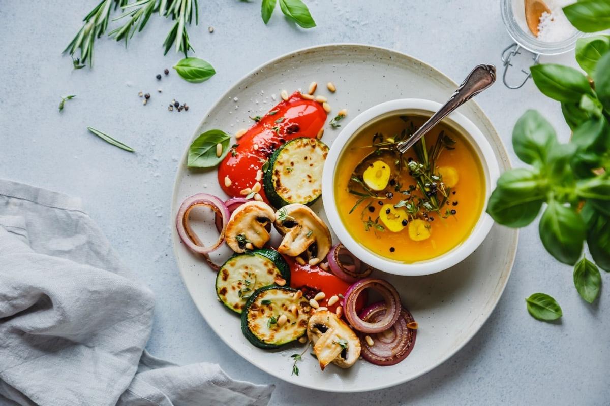 Grillgemüse und Marinade auf Teller mit Kräutern im Bild