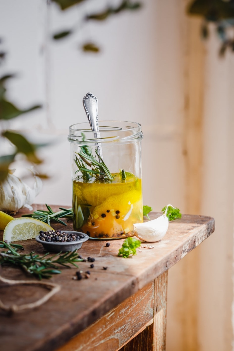 Zitronen-Ingwer-Marinade im Glas mit Zutaten auf Holztisch