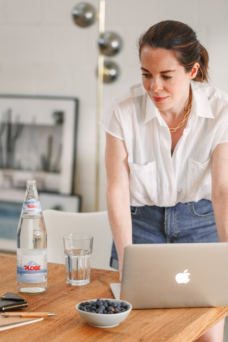 Denise am Laptop mit Flasche Wasser auf dem Tisch