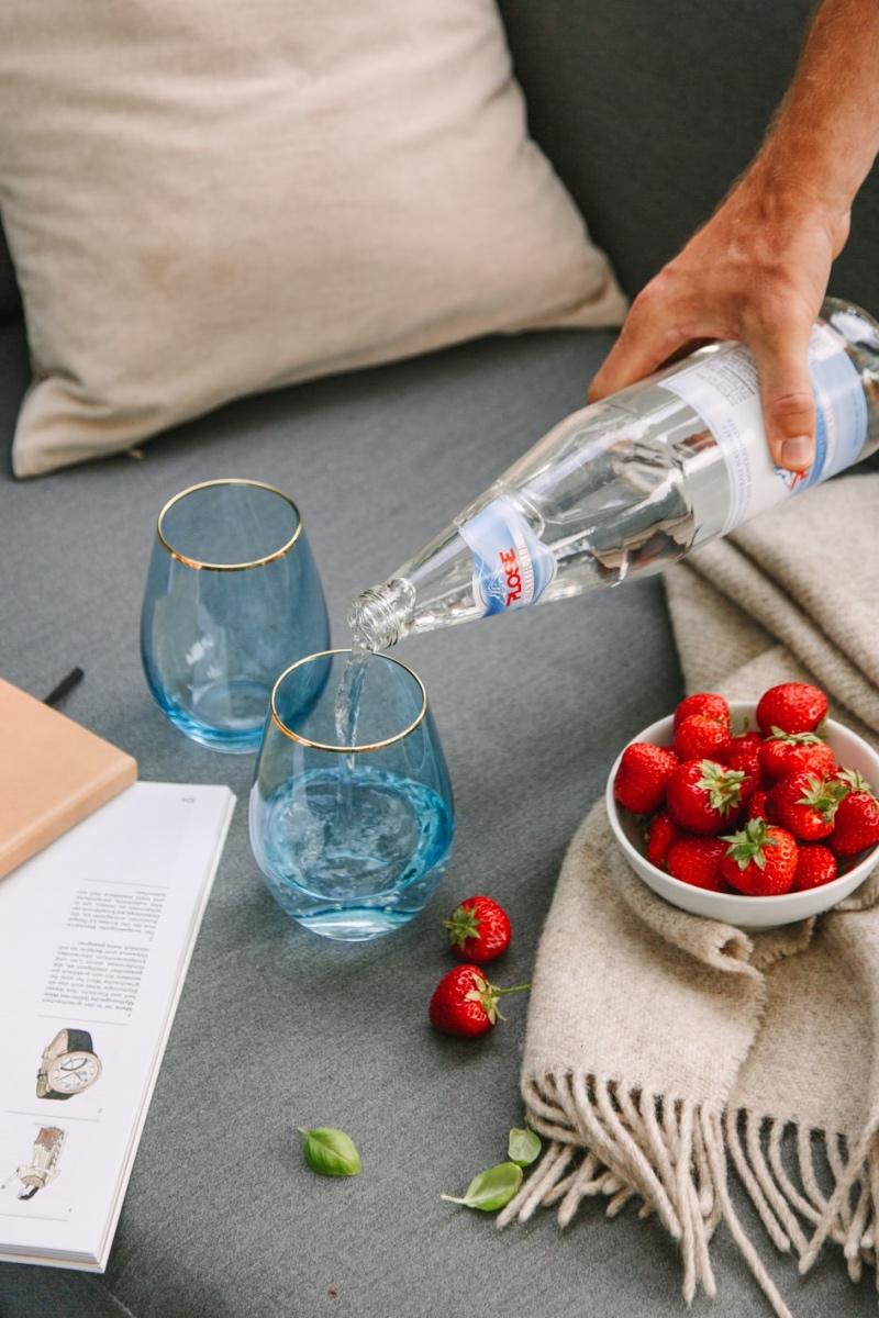 Erdbeeren und zwei Gläser, die mit Wasser befüllt werden im. Garten