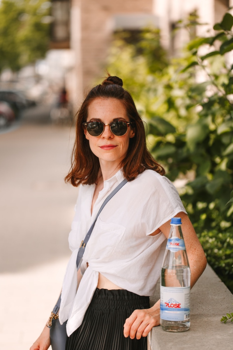 Denise mit Flasche Wasser an einer Mauer