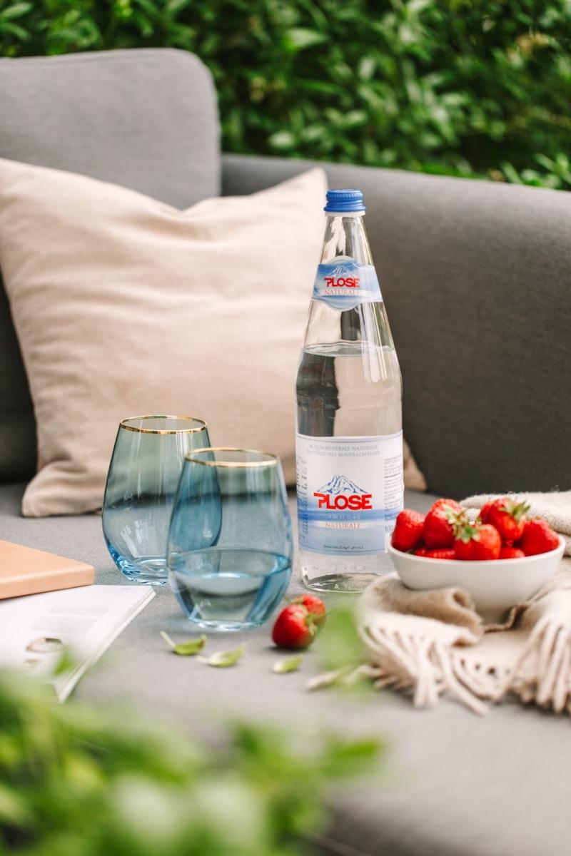 Zwei Gläser und Flasche Wasser sowie Erdbeeren im Garten