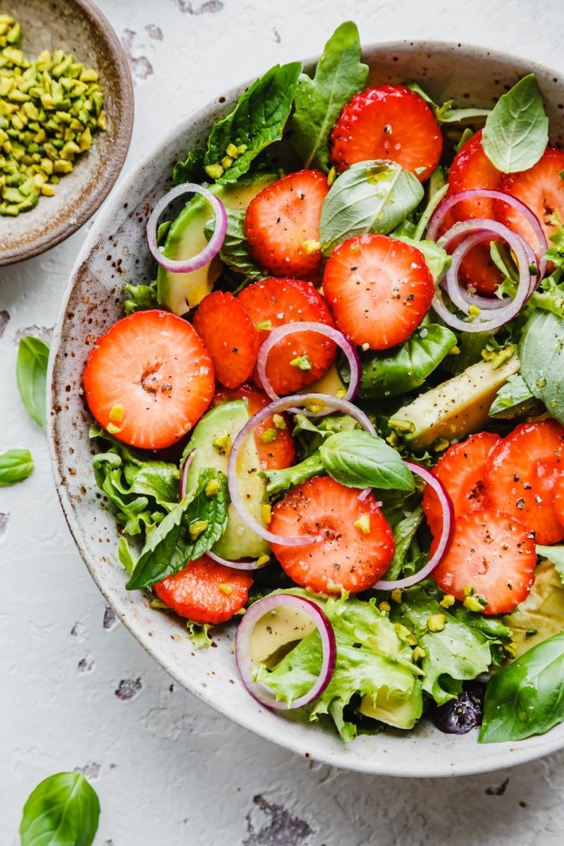 Erdbeer-Avocado-Salat in großer Schüssel und Pistazien in kleiner Schüssel