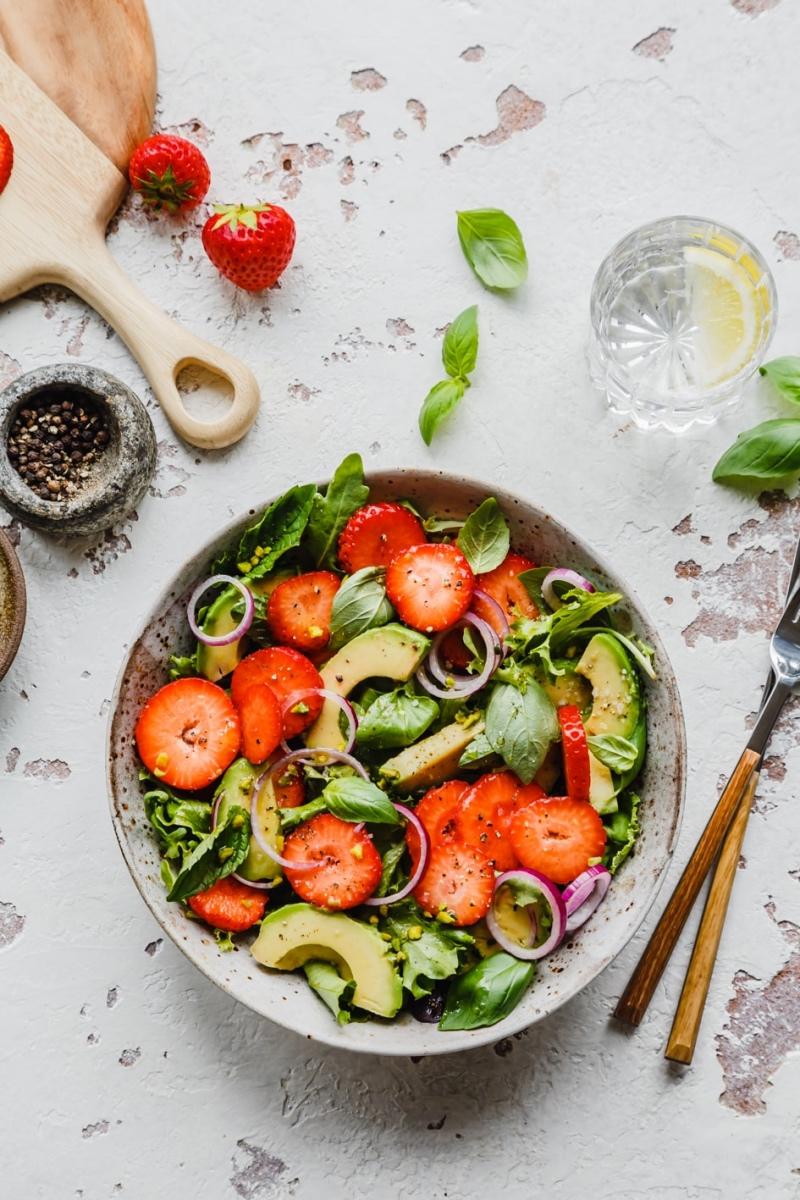 Erdbeer-Avocado-Salat in Schüssel auf Tisch mit Besteck und Zutaten